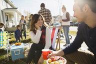 Neighbors enjoying potluck in sunny front yard - HEROF34546