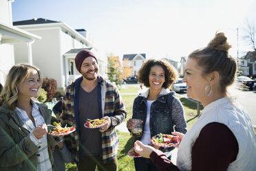 Neighbors enjoying potluck in front yard - HEROF34561