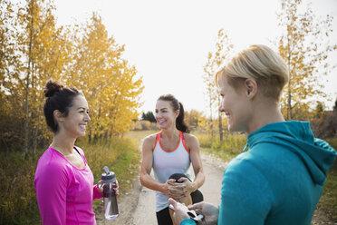 Joggers talking on autumn path - HEROF34567