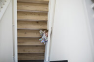 Overhead view of cute girl hiding on staircase - HEROF34690