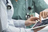 Female doctor nurse reviewing brain scan digital tablet - HEROF34789