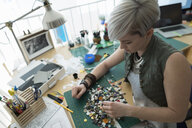 Craftswoman sorting buttons at desk in home office - HEROF34852
