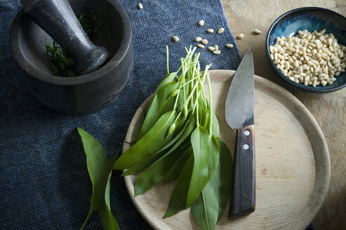 Ramson and knife on wooden board, mortar and bowl of pine nuts - ASF06365