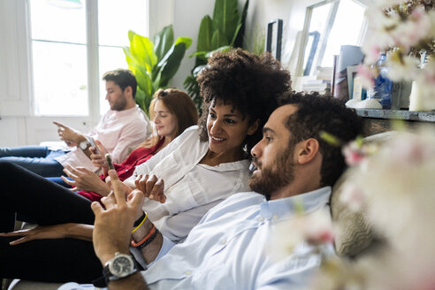 Friends sitting on couch, working casually together, using smartphones - GIOF06111
