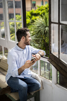 Young man sitting on bench at the window, using smartphone - GIOF06156