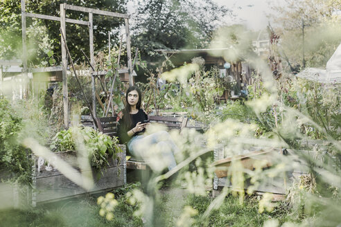 Woman with smartphone relaxing in urban garden - VGPF00007