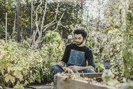 Man reading book in urban garden - VGPF00022