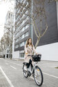 Woman riding e-bike in the city - JRFF02889