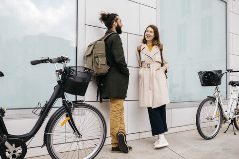 Man and woman with e-bikes standing at a building talking - JRFF02895