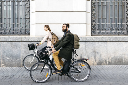 Couple riding e-bikes in the city passing a building - JRFF02901