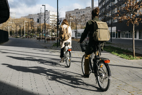 Couple riding e-bikes in the city, rear view - JRFF02904