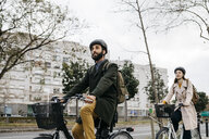 Couple riding e-bikes in the city - JRFF02910