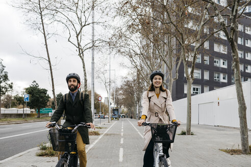 Couple riding e-bikes in the city - JRFF02913