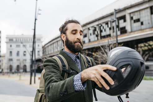 Portrait of man putting on bicycle helmet in the city - JRFF02916