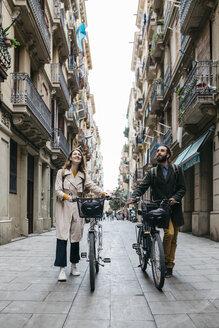 Couple pushing e-bikes exploring the city - JRFF02919