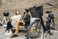 Couple sitting on a bench next to e-bikes talking - JRFF02931