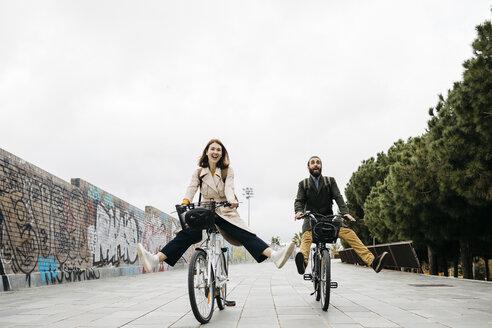 Carefree couple riding e-bikes on a promenade - JRFF02934
