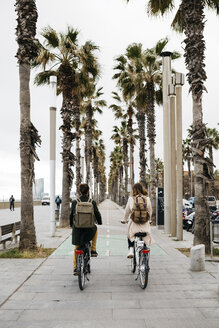 Rear view of couple riding e-bikes on a promenade - JRFF02940