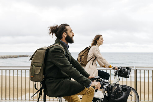 Couple riding e-bikes on beach promenade - JRFF02946
