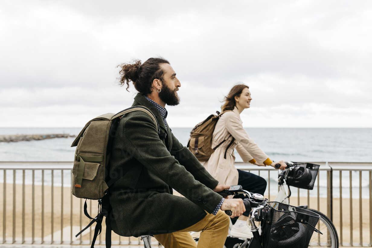 Couple riding e-bikes on beach promenade - JRFF02946 - Josep Rovirosa/Westend61