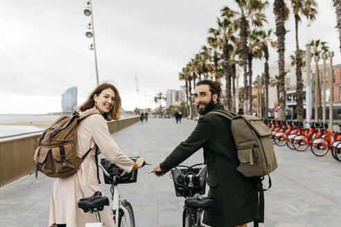 Smiling couple with e-bikes on beach promenade - JRFF02949