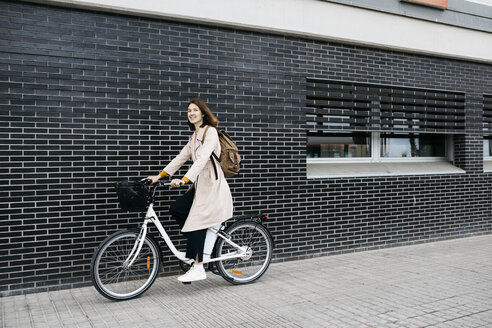 Woman riding e-bike along a brick wall in the city - JRFF02955