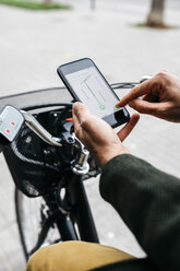 Close-up of man with e-bikeusing smartphone navigation system - JRFF02958