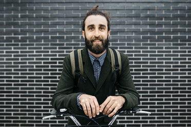 Portrait of smiling man with e-bike at a brick wall - JRFF02961