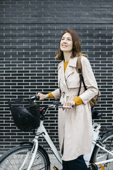 Smiling woman with e-bike at a brick wall - JRFF02964