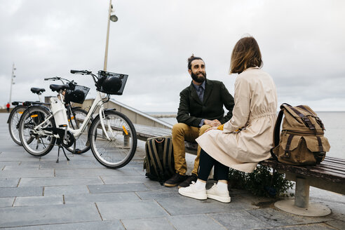 Couple sitting on a bench at beach promenade next to e-bikes talking - JRFF02970