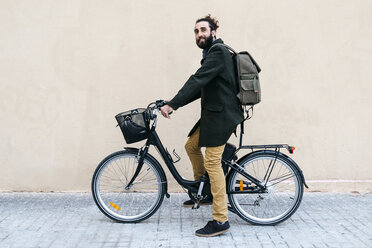 Portrait of smiling man with e-bike at a wall - JRFF02976