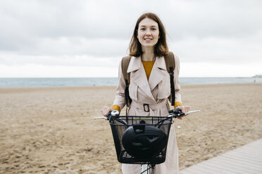Portrait of smiling woman with e-bike at the beach - JRFF02979