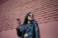 Portrait of young woman with smartphone  wearing sunglasses and black leather jacket - OCMF00370