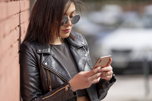 Portrait of young woman wearing sunglasses and black leather jacket looking at smartphone - OCMF00376