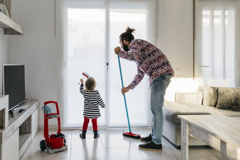 Father and little daughter cleaning the living room together - JRFF02984