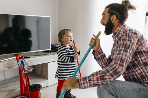 Father and little daughter having fun together while cleaning the living room - JRFF02987