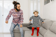 Father and little daughter dancing in the living room while listening music with headphones - JRFF02990