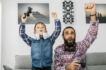 Portrait of father and son playing computer game at home - JRFF02993