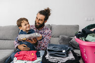 Portrait of happy father and son sitting together on the couch folding laundry - JRFF03011