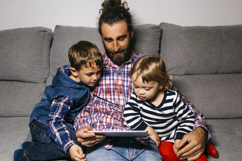 Father sitting on the couch with his children watching movies on digital tablet - JRFF03014