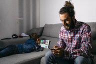 Father sitting on the couch looking at smartphone while his son using digital tablet in the background - JRFF03017