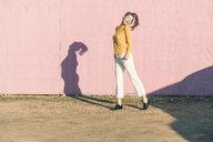 Happy young woman dancing in front of a pink wall - UUF17070