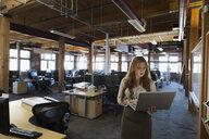 Businesswoman using laptop in office - HEROF34889