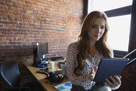 Businesswoman using digital tablet in office - HEROF34895