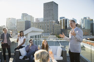 Businessman leading champagne toast on sunny urban rooftop - HEROF34988
