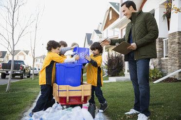 Coach and boys sports team gathering recycling neighborhood - HEROF34997
