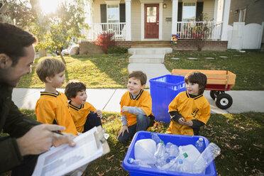 Coach and boys sports team gathering recycling neighborhood - HEROF35000