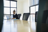 Businesswoman working at laptop in conference room - HEROF35018
