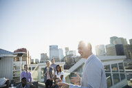 Gesturing businessman talking on sunny urban rooftop - HEROF35087