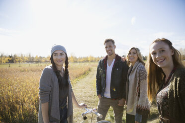 Friends with bicycle standing in sunny autumn field - HEROF35291